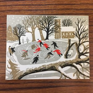 Christmas card cover with skater's on a pond and a fallen tree