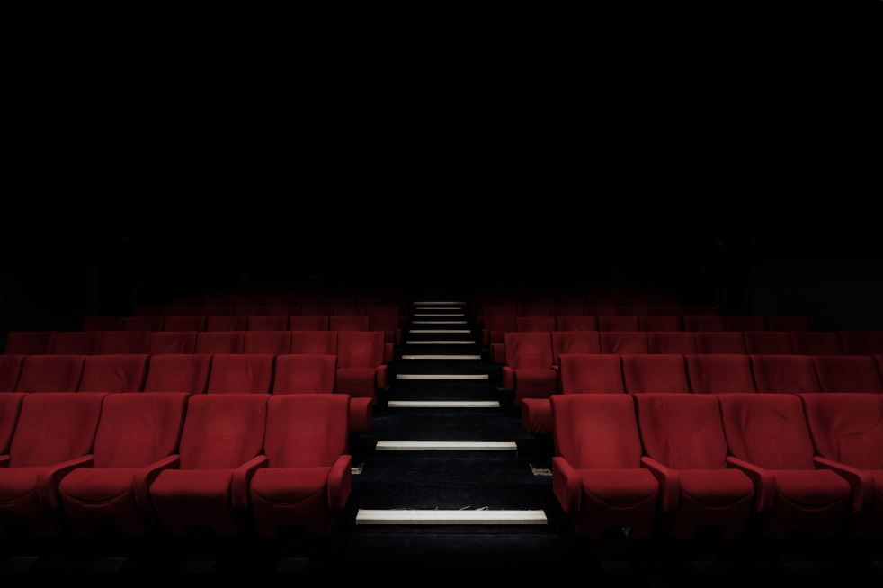 Image of rows of empty red theater seats.